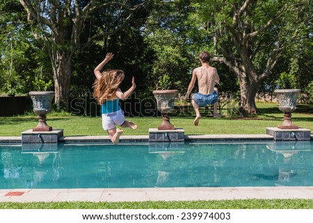 Boy Girl Jumping Pool Teenagers boy girl running  jumping into swimming pool home summer playtime - stock photo