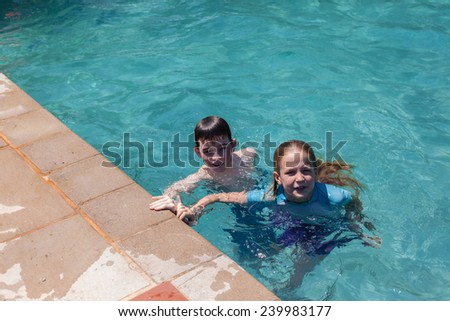 Boy Girl Swim Pool Boy girl swimming pool  home summer playtime - stock photo