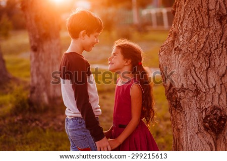 boy girl teens are holding hands romance friendship love at sunset in the summer - stock photo