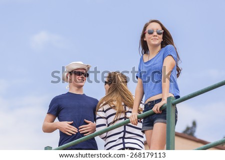 Boy Girls Beach Socializing Boy girl teenagers at beach holidays talk laughter socializing hangout. - stock photo