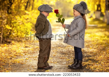 Boy gives a flower girl walking down the avenue in the park autumn day - stock photo