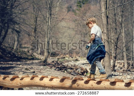 Boy goes on the mountain river bridge in spring forest - stock photo