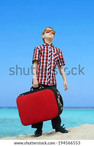 Boy going for sea vacation with a heavy luggage - stock photo