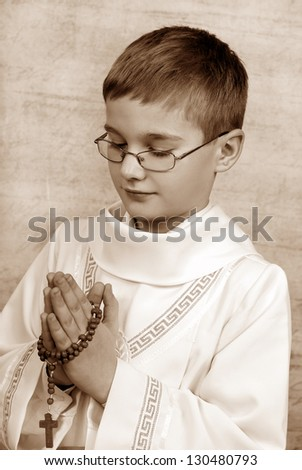 boy going to the first holy communion with a rosary (sepia) - stock photo