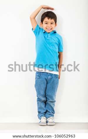 Boy growing tall and measuring himself on the wall - stock photo
