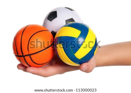 Boy hand with small volleyball, rugby, basketball and soccer balls isolated on white background - stock photo