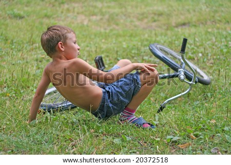 boy has fallen from a bicycle - stock photo