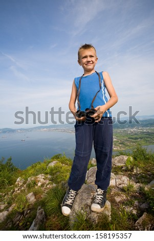 Boy hiker with binoculars standing on top of a mountain. - stock photo