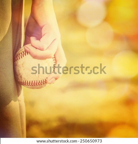 Boy holding a baseball ready to pitch.  Instagram effect. - stock photo