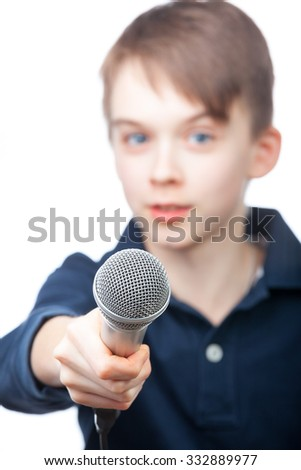 Boy holding a microphone conducting an interview, focus on microphone face is blurred - stock photo