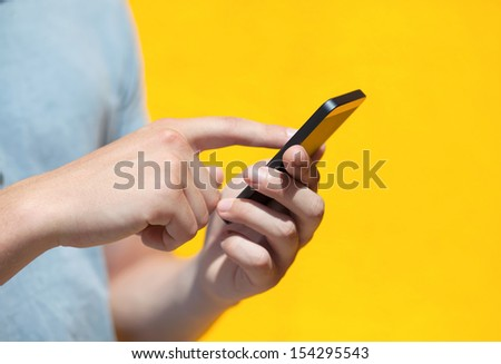boy holding a phone and a touch screen for finger against a yellow wall - stock photo