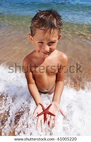 Boy holding a red starfish on sandy beach in Budva Montenegro - stock photo