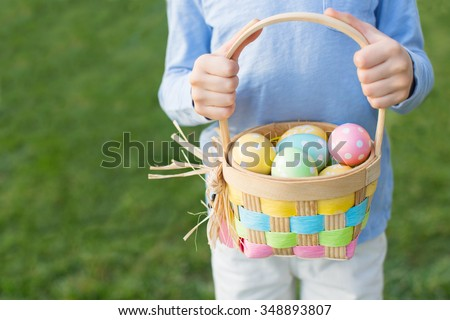 boy holding basket full of colorful easter eggs after egg hunt at spring time - stock photo