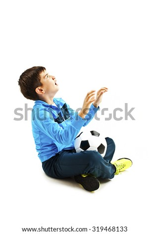 Boy holding football, looking up in shock. Isolated on a white background. Soccer ball - stock photo