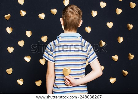 Boy holding gold heart behind his back - stock photo