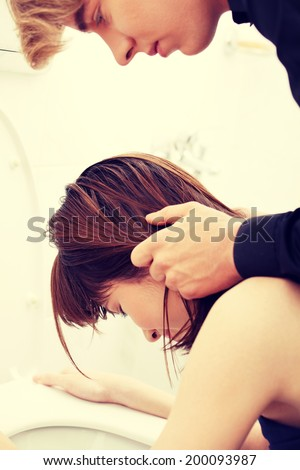 Boy holding his girlfriend head above toilet. - stock photo