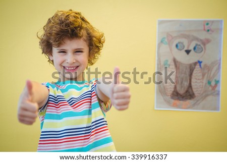 Boy holding his thumbs up and drawing beside him - stock photo