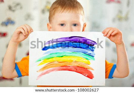 boy holding paper with painted  rainbow - stock photo