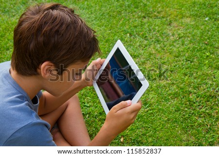 boy  holding tablet PC on green grass lawn with copy space - stock photo