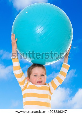 Boy holding up a huge blue ball on a background of blue sky.the concept of childhood and joy, teens - stock photo