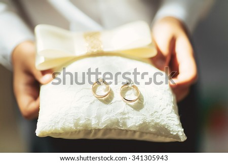 boy holds a magnificent pair of shiny golden wedding rings on a pillow - stock photo