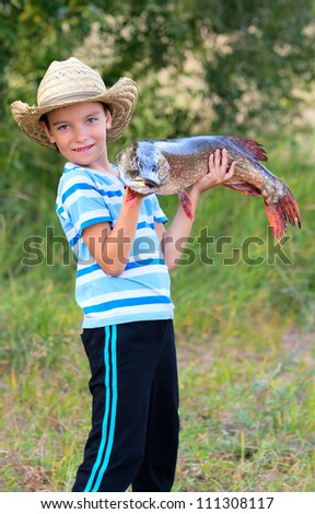 Boy holds big pike he just caught - stock photo