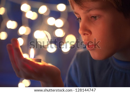 boy holds in a hand a burning candle against sparks - stock photo