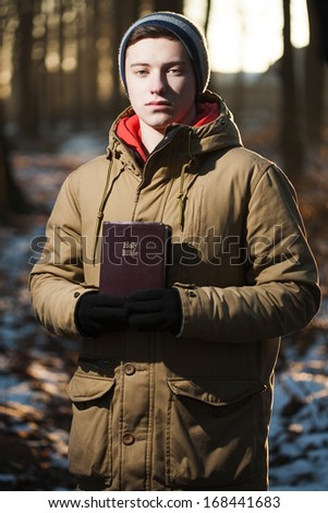 Boy holds up the Holy Bible - stock photo