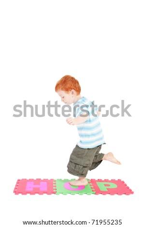 Boy hopping on word hop. Isolated on white. - stock photo