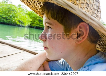 boy in a boat with straw hat in at the river in Thailand - stock photo