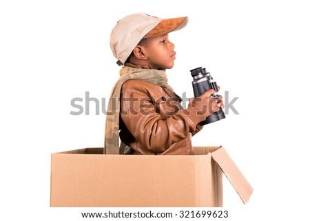 Boy in a cardboard box playing safari - stock photo