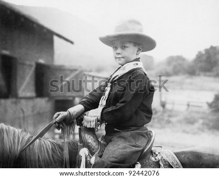 Boy in a cowboy hat on a horse - stock photo