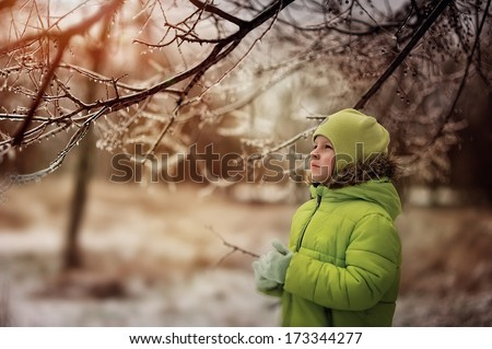 boy in a green suit walks in the park in winter with frozen trees and grass - stock photo