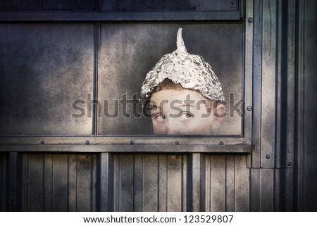 Boy in a tin foil hat peeking out of a window - stock photo