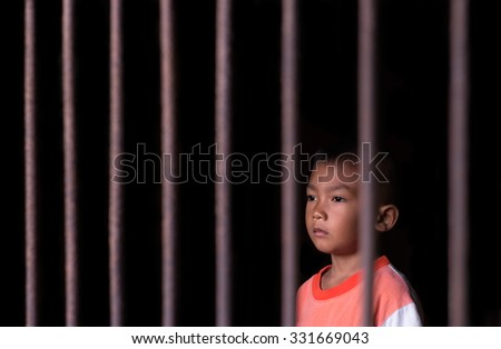 Boy in cage with eye sad and hopeless - stock photo