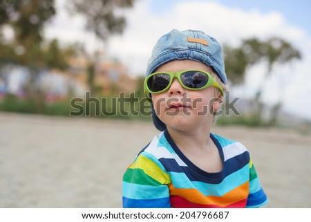 Boy in denim hat and sunglasses - stock photo