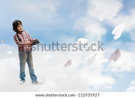 Boy in helmet pilot radio remote control with the game Paper plane - stock photo