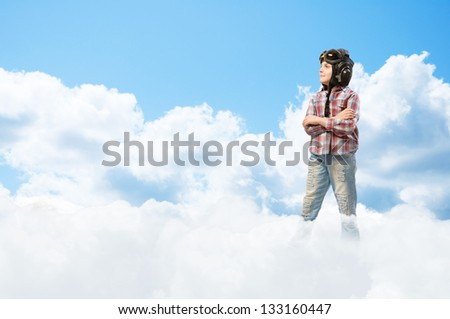 Boy in helmet pilot stands with his arms crossed in the clouds, dreaming of becoming a pilot - stock photo