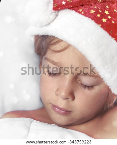 Boy in Santa hat sleeping on a pillow - stock photo