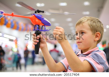 Boy in shop with toy helicopter - stock photo