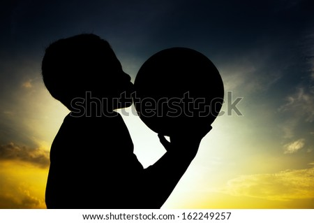 Boy in silhouette kiss the ball during sunset  - stock photo