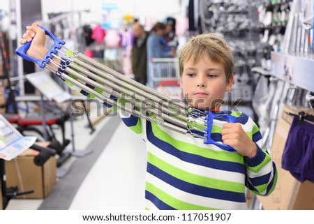 Boy in sports shop tries metal shoulder expander with springs. - stock photo