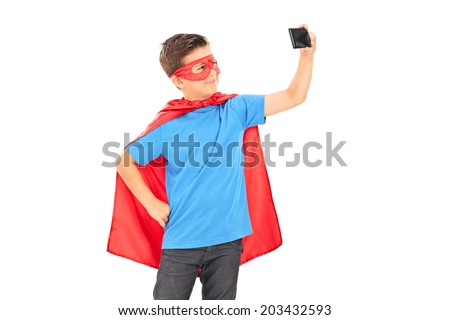 Boy in superhero costume taking a selfie isolated on white background - stock photo