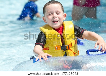 boy in swimming pool smiling, wearing a life vest - stock photo