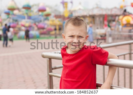 Boy in the amusement park on a background of carousels. - stock photo