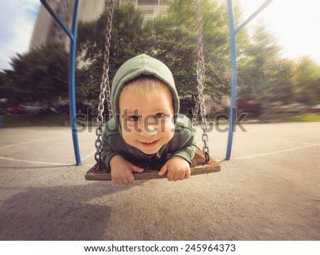 Boy in the hoodie smiling on a swing - stock photo
