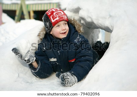 Boy in the snow/boy lying in the snow and keeps the snowball. - stock photo