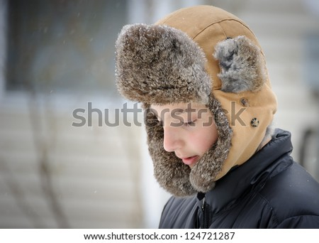 Boy in the winter in the fur hat - stock photo