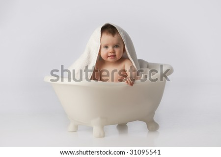 Boy in white bath tub with towel on head - stock photo