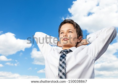 Boy in white shirt and a tie, his hands behind his back, he is confidently and happy looking into the distance. He is outside, with background a beautiful blue sky and white clouds - stock photo